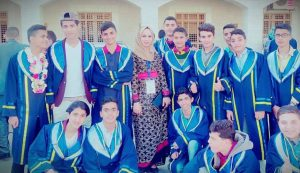 Alaa is in the center of a group of young students. Almost everyone smiles at the camera. Alaa is wearing a beautiful black and gold dress and the students are in blue robes.